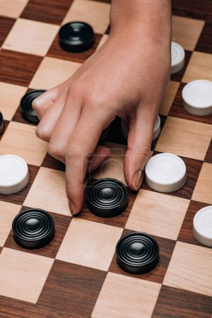 Photo for Cropped view of woman holding black checker on wooden checkerboard - Royalty Free Image