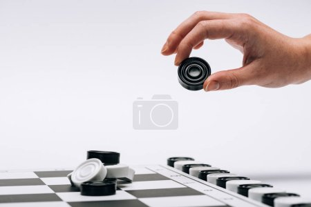 Photo for Cropped view of woman holding black checker with checkerboard isolated on white - Royalty Free Image