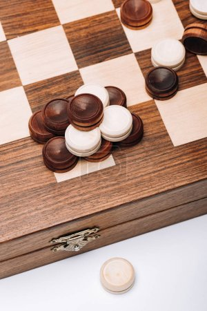 Photo for High angle view of wooden checkers on checkerboard isolated on white - Royalty Free Image