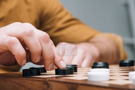 Photo for Cropped view of man playing checkers on wooden checkerboard - Royalty Free Image