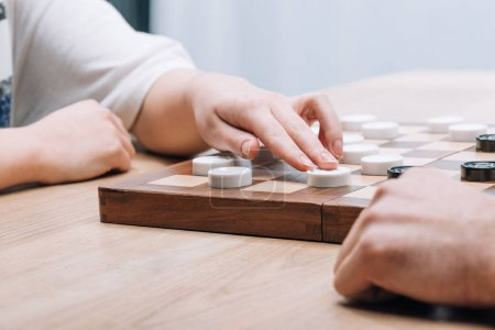 Photo for Cropped view of man and woman playing checkers at wooden table - Royalty Free Image