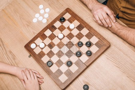 Photo for High angle view of man and woman playing checkers at wooden table - Royalty Free Image