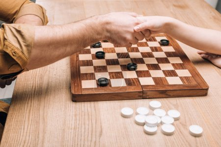 Photo for Cropped view of man and woman handshaking by checkerboard at table - Royalty Free Image