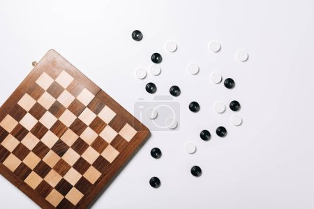 Photo for Top view of checkers by wooden checkerboard on white background - Royalty Free Image