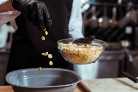 Photo for Cropped view of chocolatier adding white chocolate chips into bowl in kitchen - Royalty Free Image