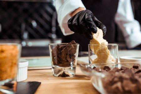 Photo pour Vue recadrée du chocolatier prenant du chocolat blanc du verre dans la cuisine - image libre de droit
