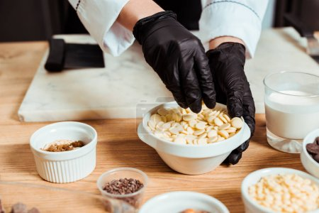 cropped view of chocolatier in black latex gloves taking white chocolate chips