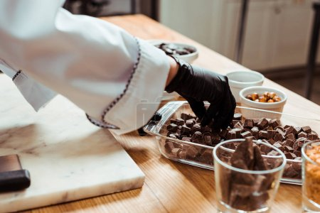 cropped view of woman taking dark chocolate cubes