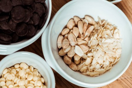 Photo for Top view of nutritious nuts near chocolate chips in bowls - Royalty Free Image