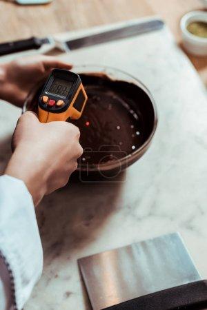 vista recortada del chocolatero que sostiene el termómetro de cocina cerca del tazón con chocolate negro derretido