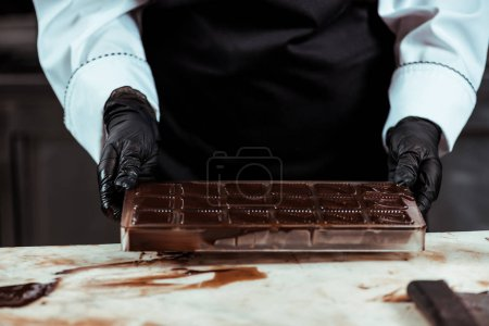 Photo for Cropped view of chocolatier in apron holding ice tray with melted chocolate - Royalty Free Image