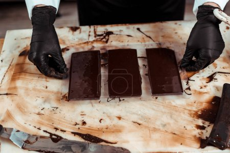 Photo for Cropped view of chocolatier in latex gloves near chocolate bars - Royalty Free Image