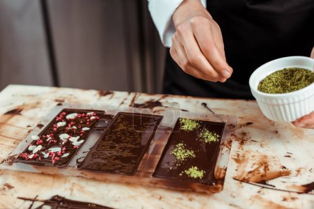 Photo for Cropped view of chocolatier adding pistachio powder on dark chocolate bar - Royalty Free Image