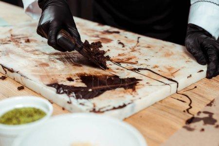 Photo pour Vue recadrée du chocolatier en gants de latex noir raclant les copeaux de chocolat noir - image libre de droit