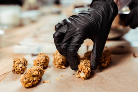 Photo for Cropped view of chocolatier in black latex glove taking delicious chocolate candy with flakes - Royalty Free Image