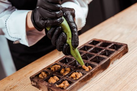 cropped view of chocolatier holding pastry bag with caramelized nuts near chocolate molds