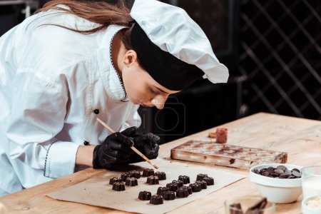 Photo for Attractive chocolatier holding brush with gold powder near prepared chocolate candies - Royalty Free Image