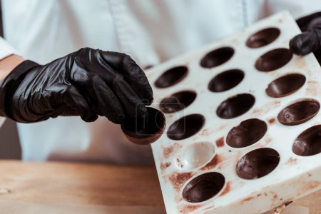 cropped view of chocolatier holding chocolate candy