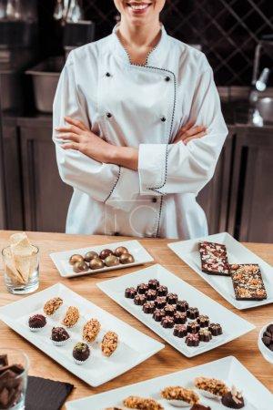 Photo pour Vue en coupe d'un chocolatier gai debout aux bras croisés près de délicieux bonbons de chocolat sur des assiettes - image libre de droit