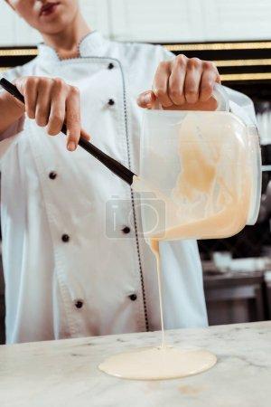 vista recortada de chocolatero verter chocolate blanco derretido en la superficie de mármol