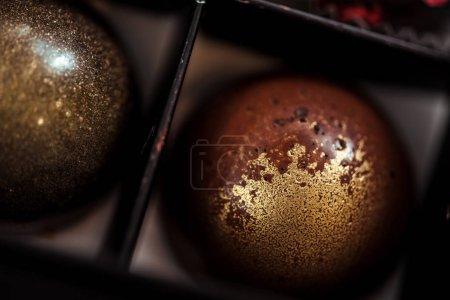 Photo pour Gros plan de boules de chocolat sucré avec poudre dorée en boîte - image libre de droit