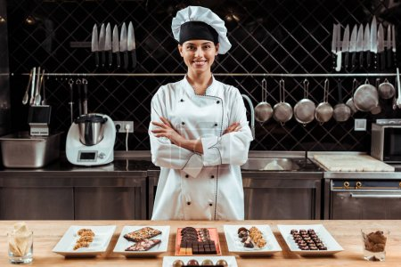 Photo for Happy chocolatier in chef hat standing with crossed arms near tasty chocolate candies on plates - Royalty Free Image
