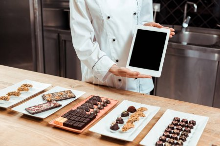 Photo for Cropped view of chocolatier in holding digital tablet with blank screen near tasty chocolate candies on plates - Royalty Free Image