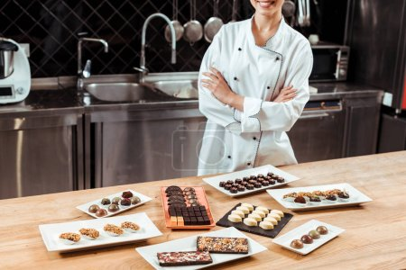 cropped view of cheerful chocolatier standing with crossed arms near tasty chocolate candies on plates