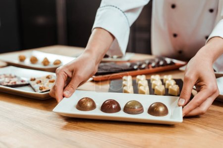 Photo for Cropped view of chocolatier touching plate with sweet and fresh chocolate candies - Royalty Free Image