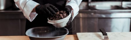Photo for Panoramic shot of chocolatier in latex gloves adding dark chocolate chips into bowl - Royalty Free Image