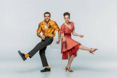 Photo pour Des danseurs de style regardant la caméra tout en dansant boogie-woogie sur fond gris - image libre de droit