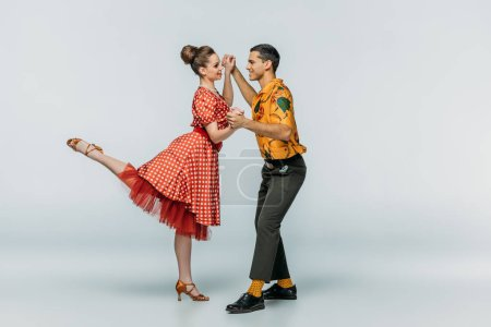 cheerful dancers holding hands while dancing boogie-woogie on grey background