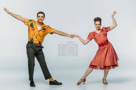 Photo pour Danseurs élégants tenant la main tout en dansant boogie-woogie sur fond gris - image libre de droit