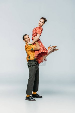 Photo pour Élégant danseur tenant partenaire tout en dansant boogie-woogie sur fond gris - image libre de droit