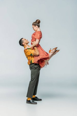Photo for Side view of handsome dancer holding partner while dancing boogie-woogie on grey background - Royalty Free Image