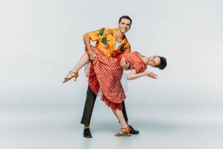 Photo pour Danseuse élégante partenaire de soutien tout en dansant boogie-woogie sur fond gris - image libre de droit