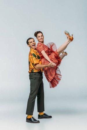 Photo pour Joyeux danseur tenant partenaire tout en dansant boogie-woogie sur fond gris - image libre de droit