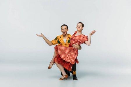 Photo pour Belle danseuse debout sur le genou et partenaire de soutien tout en dansant boogie-woogie sur fond gris - image libre de droit