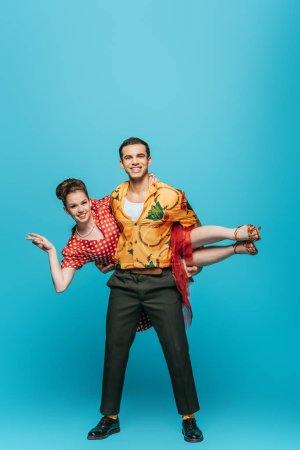 Photo for Handsome dancer holding partner while dancing boogie-woogie on blue background - Royalty Free Image