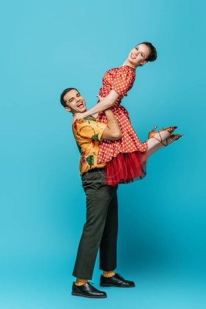 Photo for Cheerful dancer holding partner while dancing boogie-woogie on blue background - Royalty Free Image