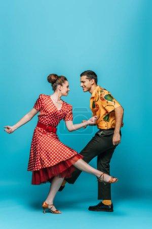 Photo pour Danseurs souriants se regardant mutuellement pendant qu'ils dansent boogie-woogie sur fond bleu - image libre de droit