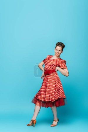 Photo pour Joyeuse, danseuse élégante regardant la caméra tout en dansant boogie-woogie sur fond bleu - image libre de droit
