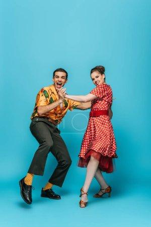 Photo pour Danseurs joyeux tenant la main tout en dansant boogie-woogie sur fond bleu - image libre de droit