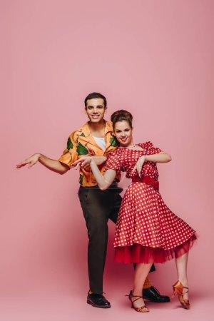 bailarines elegantes mirando a la cámara mientras bailan boogie-woogie sobre fondo rosa