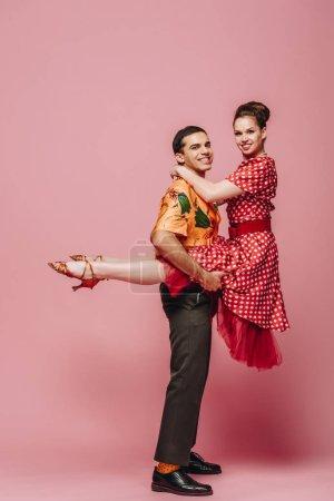 Photo pour Homme gai tenant femme tout en dansant boogie-woogie sur fond rose - image libre de droit