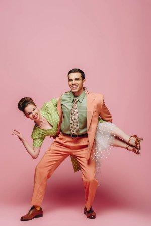 elegante bailarina sosteniendo chica mientras baila boogie-woogie sobre fondo rosa