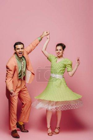 Photo pour Danseurs joyeux tenant la main tout en dansant boogie-woogie sur fond rose - image libre de droit
