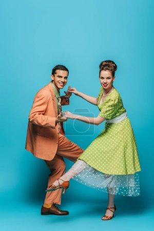 Photo pour Des danseurs joyeux regardent la caméra pendant qu'ils dansent boogie-woogie sur fond bleu - image libre de droit