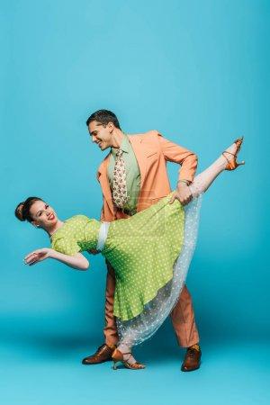 Photo pour Danseuse élégante soutien fille tout en dansant boogie-woogie sur fond bleu - image libre de droit