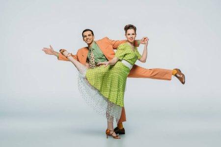 Photo pour Danseurs heureux regardant la caméra tout en dansant boogie-woogie sur fond gris - image libre de droit